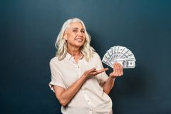 Smiling mature old woman showing money holding in hands. Photo of smiling mature old woman isolated over dark blue background. Looking camera showing money Royalty Free Stock Image