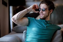 Photo of smiling nice muscular male in blue T-shirt taking off sunglasses Royalty Free Stock Photo