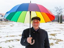 Smiling senior man. Photo of smiling senior man under umbrella walking in the park Stock Image