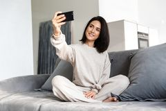 Photo of smiling woman 30s taking selfie on cell phone, while sitting on couch in bright apartment royalty free stock photo