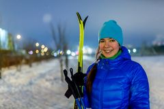 Photo of smiling woman with skis in winter forest. On blurred background Stock Images