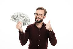 Smiling young man holding money showing thumbs up. Photo of smiling young man standing isolated over white background. Looking camera holding money showing royalty free stock photos