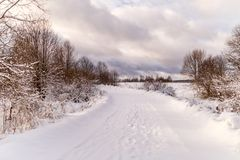 Photo of snowy landscape with cloudy sky and road. In winter Royalty Free Stock Photo