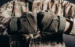 Soldier in tactical gloves showing fists