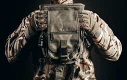 Soldier in gloves holding tactical leg bag