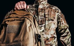 Soldier in gloves holding tactical backpack