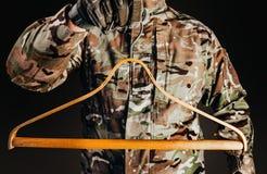 Soldier in gloves holding wooden shirt hanger