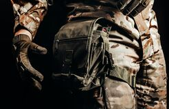 Soldier in tactical gloves using leg bag