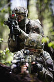 Photo of soldiers on reconnaissance. In woods during day stock image