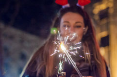 Photo of Sparkler with woman in background. Happy New Year. Stock Images