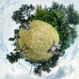 Photo sphere of a paintball field with barrels, trees and wooden buildings. Polar panorama. 360 degrees.  royalty free stock image