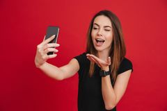 Photo of splendid woman in black t-shirt flirting and making air. Kiss with her palm on mobile phone isolated over red background Royalty Free Stock Photo