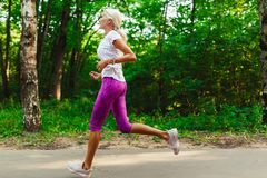 Photo of sports girl jogging in park Royalty Free Stock Images