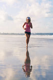 Photo of sports girl runs along the beach. Reflected on the sand Royalty Free Stock Photos