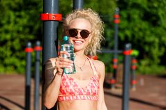 Photo of sports woman wearing sunglasses with bottle of water near horizontal bar in park. On summer day stock photos