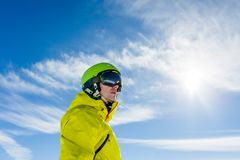 Photo of sporty man wearing mask and helmet against blue sky. During day Royalty Free Stock Image