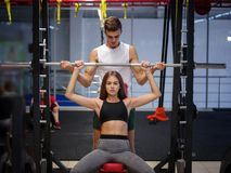 A strong woman with beautiful athletic body doing exercises with a barbell on a gym background. Bodybuilding concept. A photo of a sporty young women training Stock Image