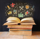 Photo of stack of old books. top book is open with set of infographics. imagination and education concept. royalty free stock photo