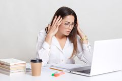 Photo of stressful woman looks with puzzled expression into screen, wears formal shirt, busy with making financial report, feels w royalty free stock photo