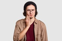 Photo of stressful youngster with small beard keeps hand on cheek, suffers from toothache, keeps eyes shut, dressed in stylish clo. Thes, big round spectacles stock photography