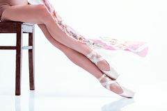 Ballerina`s feet in pointe and with silk scarf on white background stock photo