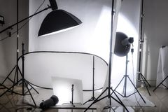 Photo studio with lights and white background. Photo of an empty photographic studio with modern lighting stock image