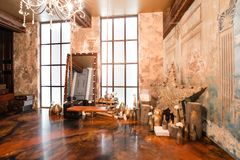Photo studio. Loft interior with mirror, candles, brick wall, large window, living room, coffee table in modern design. Interior with fireplace, candles, skin of Stock Image