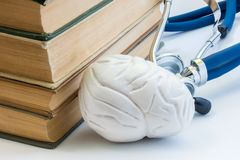 Photo study of brain, mental health, anatomy, structure, function in medicine school, college, university. Model of brain is locat. Ed next to pile of medical royalty free stock image