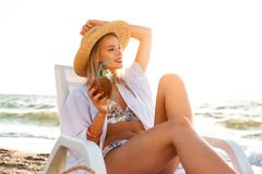 Photo of stunning blonde woman 20s in straw hat drinking exotic. Cocktail while lying in deck chair at sea coast during summer sunrise Stock Images