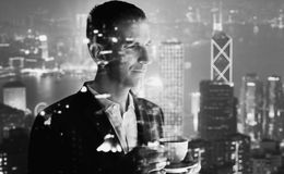 Photo of stylish adult businessman wearing trendy suit and holding cup coffee. Double exposure, panoramic view contemporary city s royalty free stock photos