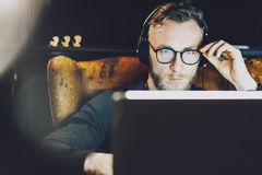 Photo stylish bearded man wearing glasses working modern loft office. Young banker sitting vintage chair,listening music