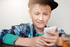 A photo of stylish little boy wearing trendy cap and shirt using video conferencing app on mobile phone, talking online to his fri Royalty Free Stock Images