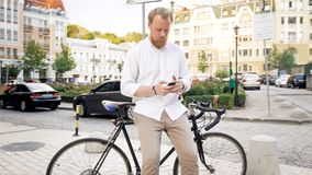 Photo of stylish young man sitting on bicycle and browsing internet on smartphone. Photo of stylish man sitting on bicycle and browsing internet on smartphone Royalty Free Stock Photography