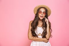 Photo of stylish woman 20s wearing sunglasses and straw hat smiling at camera, isolated over pink background. Photo of stylish woman 20s wearing sunglasses and stock images