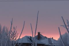 Cold frosty morning. Sunrise over the snowy roofs. royalty free stock image