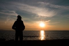 Photo of the sunset with the silhouette of a young man. royalty free stock photos