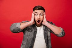 Photo of surprised man 30s wearing beard in jeans jacket grabbin. G head and reacting emotionally isolated over red background Stock Photography