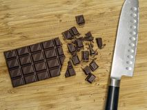 Chopping chocolate bar for baking royalty free stock photo