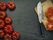 Marmande tomatoes with knife and cutting board. Photo of a table top with Marmande tomatoes, a knife, and slices on a cutting board stock image