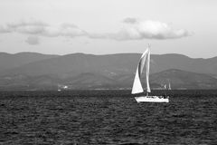 Sailboats sail on the sea on a hilly background royalty free stock photo