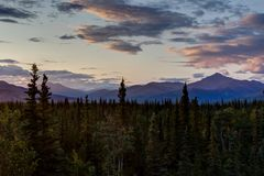 Sunrise with trees and towards mountains in Alaska United States. Photo taken in Denali National Park Alaska, United States of America. Denali National Park is stock photos