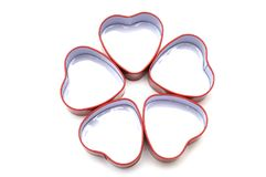 Five heart shaped metal containers arranged in a petal pattern. A photo taken on five small red heart shaped metal containers arranged in a flower petal pattern royalty free stock images