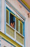 Woman in the window. Photo taken in Las Peñas neighborhood located in Guayaquil, Ecuador. Place renowned for its colonial architecture. Houses are painted in a Royalty Free Stock Image
