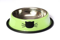A luminous green colored pet feeding bowl. A photo taken on a luminous green colored pet feeding bowl with cat head imprint and friction rubber against a white royalty free stock photos
