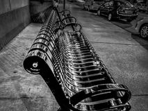 The bench on the sidewalk. Photo taken in Montreal, Quebec, Canada in autumn 2013. This black and white photo represents the tranquility of a city on a weekday Royalty Free Stock Photo