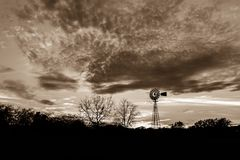 Sunset with a Windmill in Ingram Texas, Sepia Tone. Photo taken in November 2017 in Ingram Texas. Windmill in a line of trees silhouetted, sepia toned photo Royalty Free Stock Images