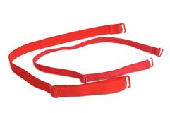A pair of different sizes red brassiere straps. A photo taken on pair of red brassiere straps against a white backdrop. They are of different size and width royalty free stock photography