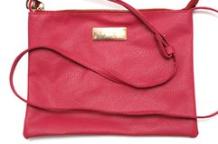 A red pink women`s sling bag. A photo taken on a pink red colored women`s sling bag against a white backdrop Stock Photography