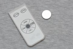 Small white and grey remote controller and a button cell coin lithium battery. A photo taken on a small white and light grey colored remote controller for air Stock Photography