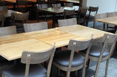 Some empty wooden chairs and tables. A photo taken on some empty wooden brown chairs and tables in a public space royalty free stock images